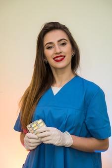 Glimlachende arts die pillen in blaar aanbiedt. vrouw die medisch uniform en beschermende handschoenen draagt