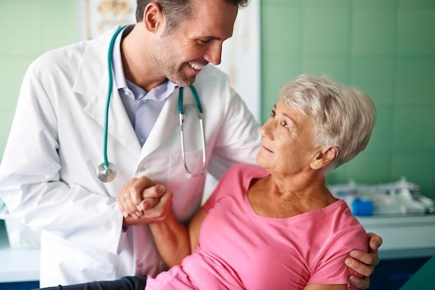 Glimlachende arts die van hogere vrouw helpt