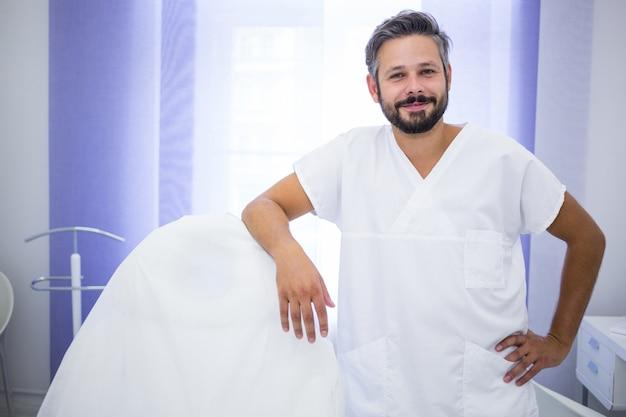 Glimlachende arts die zich in kliniek bevindt