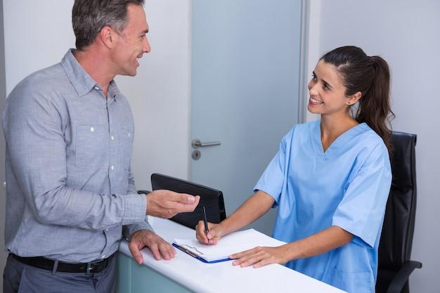 Glimlachende arts en patiënt die bij bureau spreken