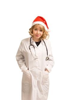 Glimlachende arts in een laboratoriumjas en kerstmuts klaar om kerstmis te vieren met haar patiënten in het ziekenhuis