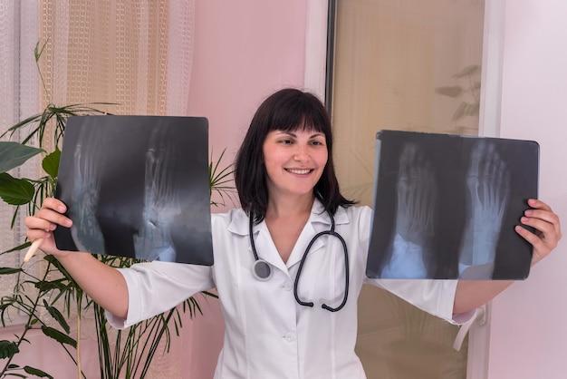 Glimlachende arts met de röntgenfoto van de patiënt in handen