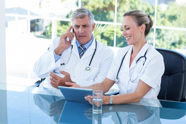 Glimlachende artsen die aan tablet samenwerken