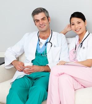 Glimlachende artsen die en koffie ontspannen drinken