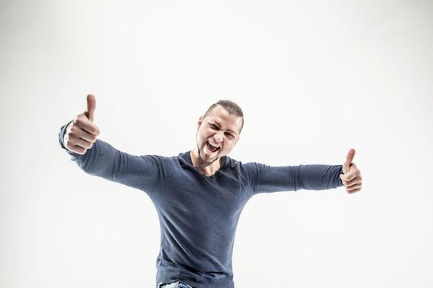 Glimlachende atletische kerelbodybuilder in jeans en t-shirt die duimen omhoog gebaar tonen.