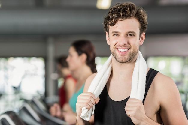 Glimlachende atletische mens die aan camera in gymnastiek glimlachen
