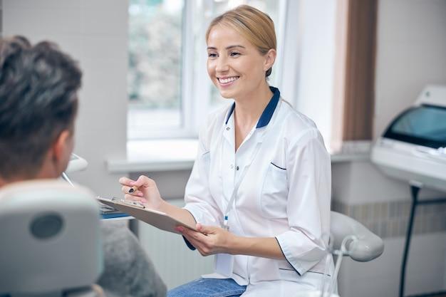 Glimlachende attente arts zit in de buurt van tandartsstoel met man en luistert naar zijn klachten
