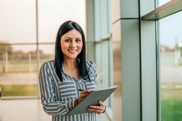 Glimlachende auto verkoopster vrouw met documenten.