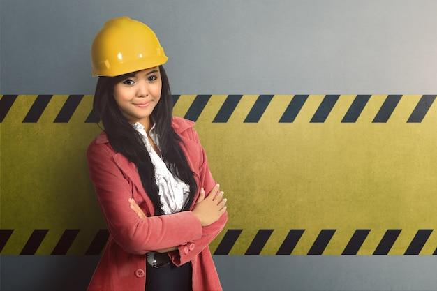 Glimlachende aziatische arbeidersvrouw met gele helm en gekruiste hand