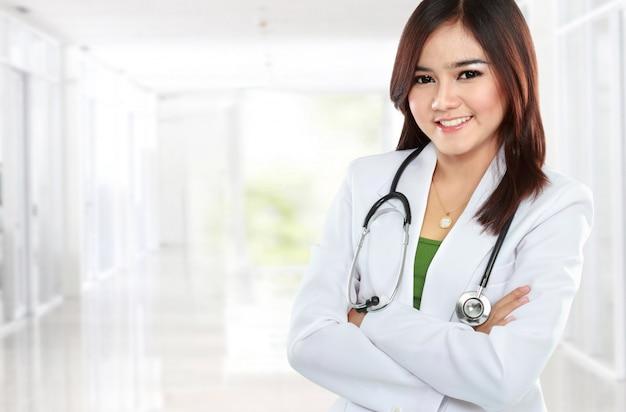 Glimlachende aziatische arts die een witte laag en een stethoscoop met gekruist wapen dragen