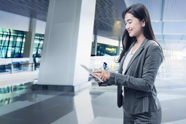 Glimlachende aziatische bedrijfsvrouw die digitale tablet gebruiken