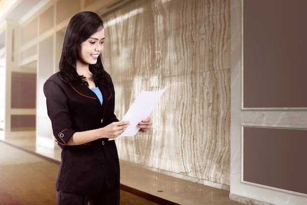 Glimlachende aziatische bedrijfsvrouw die een document houdt