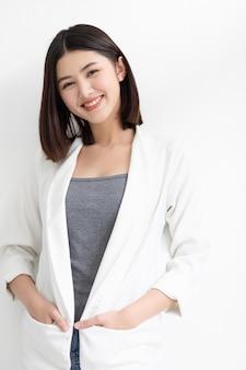 Glimlachende aziatische bedrijfsvrouw die en zich de camera bevindt bekijkt