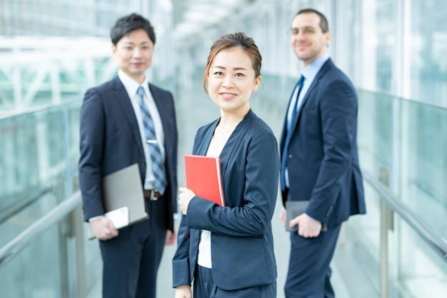 Glimlachende aziatische bedrijfsvrouw en haar commercieel team
