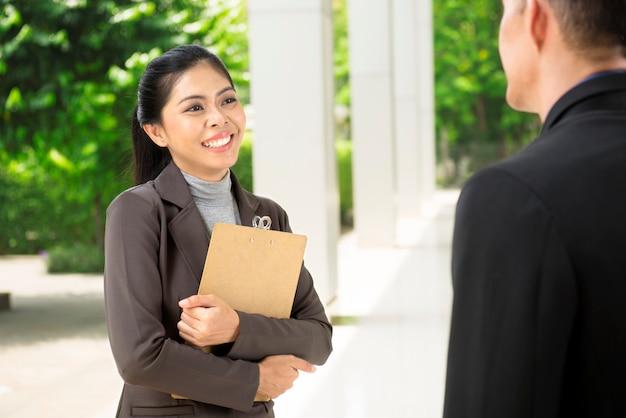 Glimlachende aziatische bedrijfsvrouw terwijl het spreken aan haar partner