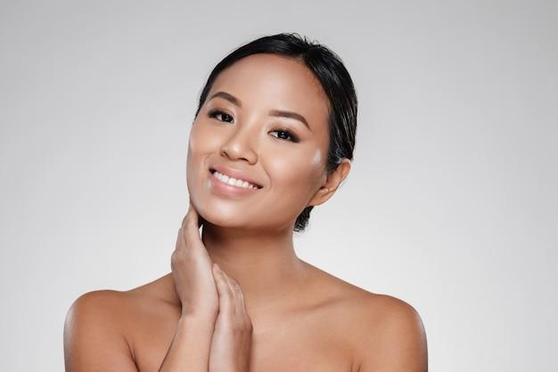 Glimlachende aziatische dame wat betreft haar duidelijke huid en het kijken camera