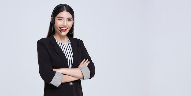 Glimlachende aziatische de telefoniste van de onderneemsterklantenondersteuning die over grijze achtergrond wordt geïsoleerd. callcenter en klantenserviceconcept.