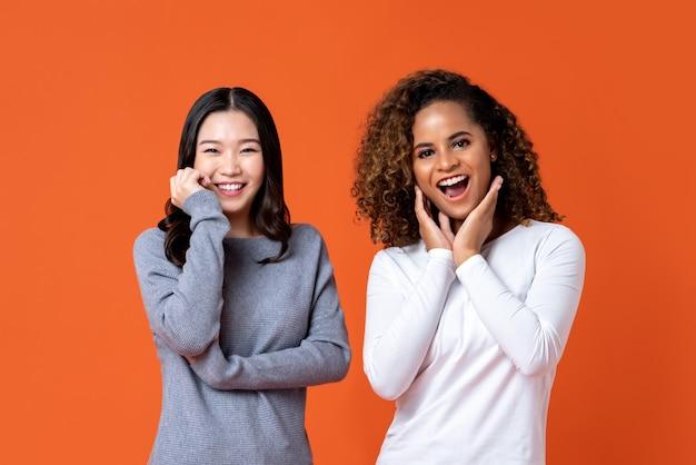 Glimlachende aziatische en afrikaanse amerikaanse vrouwenvrienden in verrast gebaar