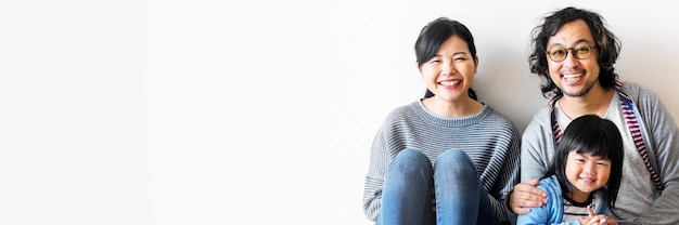 Glimlachende aziatische familie met een dochter die op de lege ruimtebanner van de vloer zit