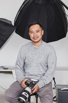 Glimlachende aziatische fotograaf die camera in studio zit en vasthoudt