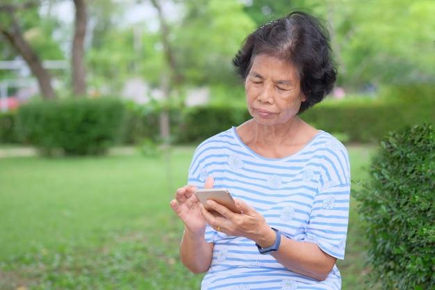 Glimlachende aziatische hogere vrouw die smartphonezitting gebruiken bij tuin