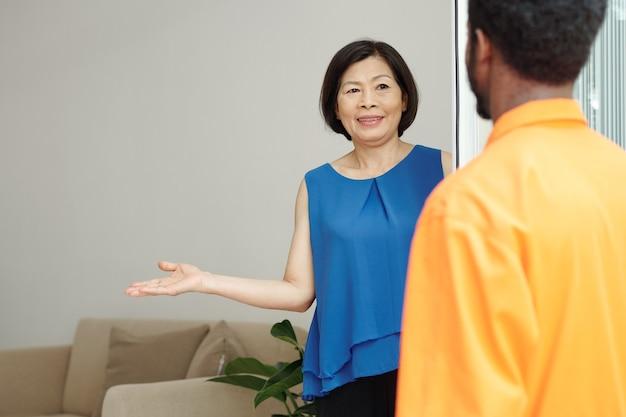 Glimlachende aziatische huiseigenaar in blauwe blouse die de richting naar de kamer wijst terwijl hij de schoonmaker begroet in een oranje bodysuit