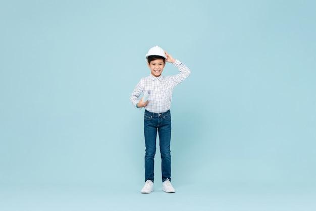Glimlachende aziatische jongen die ingenieurshelm dragen en blauwdruk houden