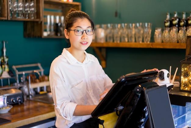 Glimlachende aziatische kassier die in koffie werkt en camera bekijkt.