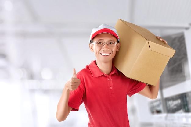 Glimlachende aziatische koeriersmens met rode eenvormig leverend pakket