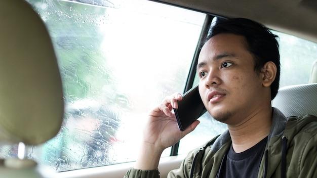Glimlachende aziatische man in een auto terwijl aan de telefoon