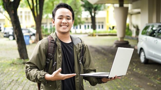 Glimlachende aziatische man met een rugzak wees op de laptop