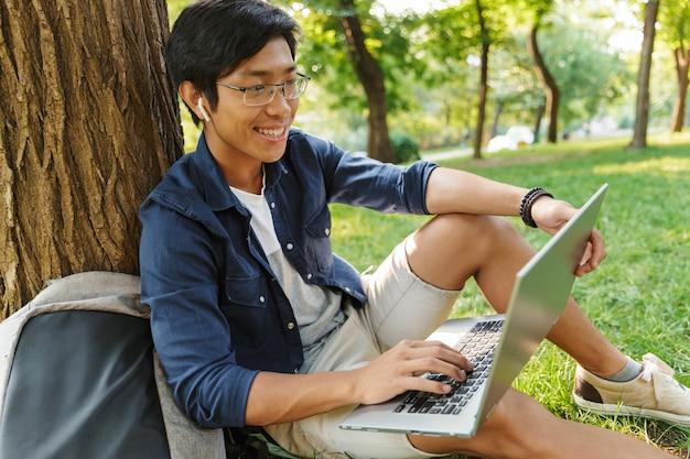 Glimlachende aziatische mannelijke student in oogglazen die laptop computer met behulp van zittend dichtbij de boom in park