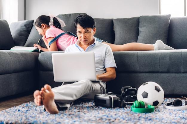 Glimlachende aziatische mens die gebruikend laptop computer het werken en het gesprek van de videoconferentievergadering met zijn meisjesdochter leren die lezingsboek leren en kennis thuis bestuderen. werk van huisconcept
