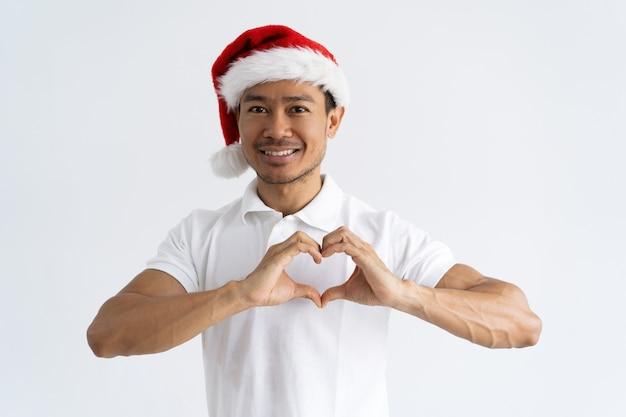 Glimlachende aziatische mens die hartgebaar met zijn handen maakt