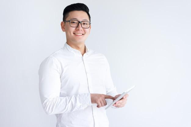 Glimlachende aziatische mens die tabletcomputer met behulp van