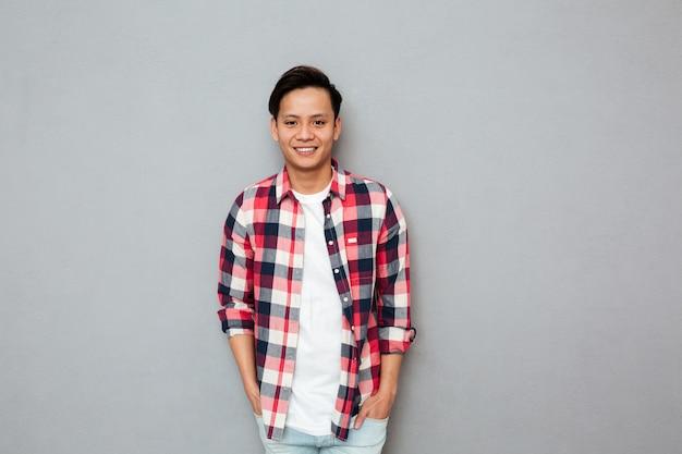 Glimlachende aziatische mens die zich over grijze muur bevindt.