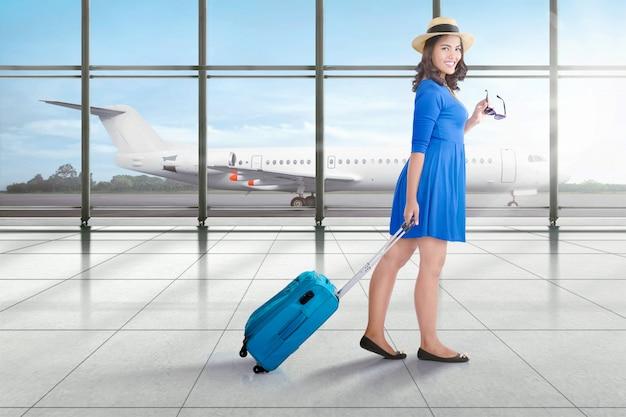Glimlachende aziatische reizigersvrouw met koffer het lopen