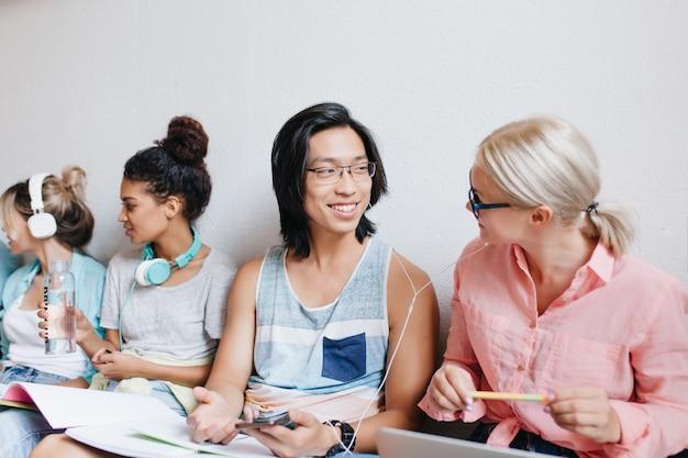 Glimlachende aziatische student die favoriete lied met blonde vrouw bespreekt tijdens het voorbereiden van lessen. indoor portret van tevreden universiteitsvrienden praten over examens en luisteren muziek in witte koptelefoon.