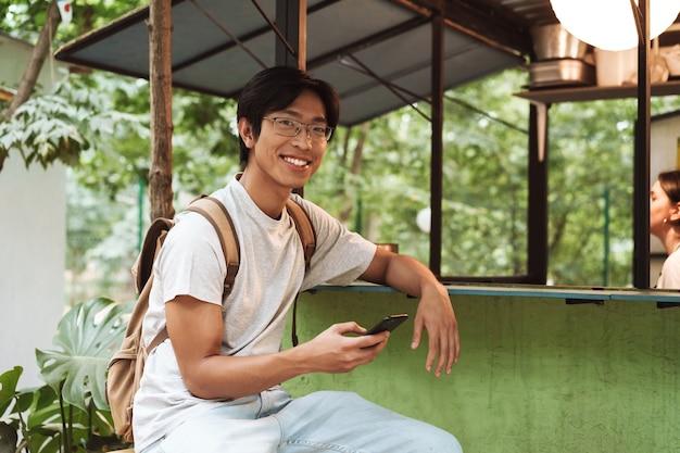 Glimlachende aziatische studentenmens die rugzak draagt