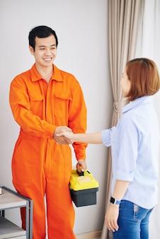 Glimlachende aziatische technicus in oranje uniform met toolbox hand van huisvrouw schudden