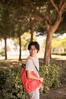 Glimlachende aziatische tienermens die terug eruit ziet