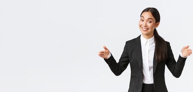 Glimlachende aziatische verkoopster die product verkoopt aan klant, groot object vormgeeft en vriendelijk grijnst naar de camera. zakenvrouw introduceert haar project aan het publiek, adverteert groot appartement, witte achtergrond