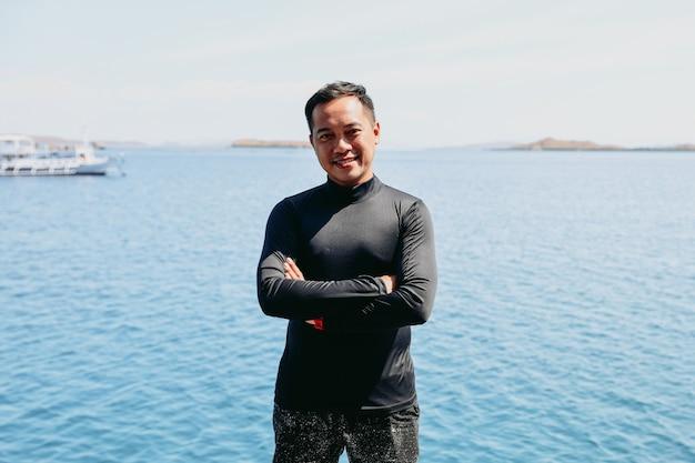 Glimlachende aziatische volwassen man op vakantie in de zee