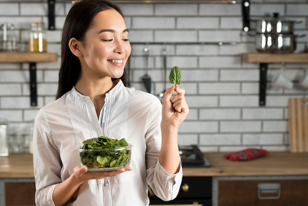 Glimlachende aziatische vrouw die basilicumblad in keuken bekijkt