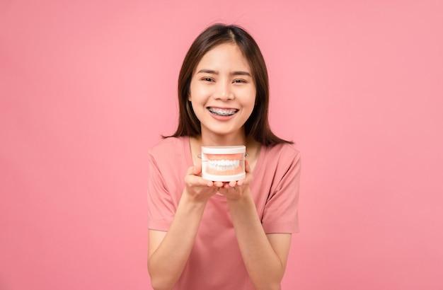 Glimlachende aziatische vrouw die beugels draagt met tandmodel op roze achtergrond, concept mondhygiëne en gezondheidszorg