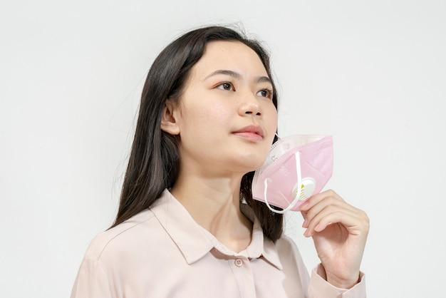 Glimlachende aziatische vrouw die een masker draagt