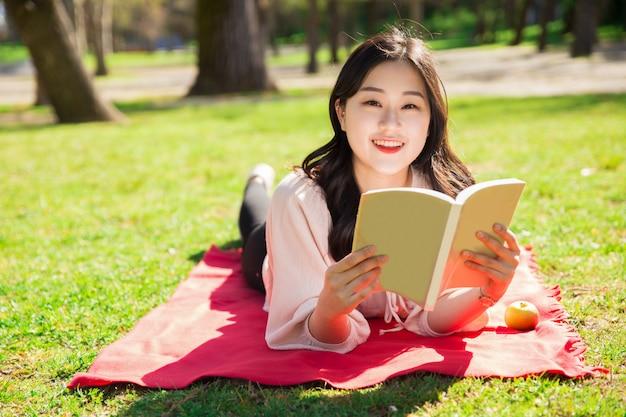 Glimlachende aziatische vrouw die en boek op gazon ligt lezen