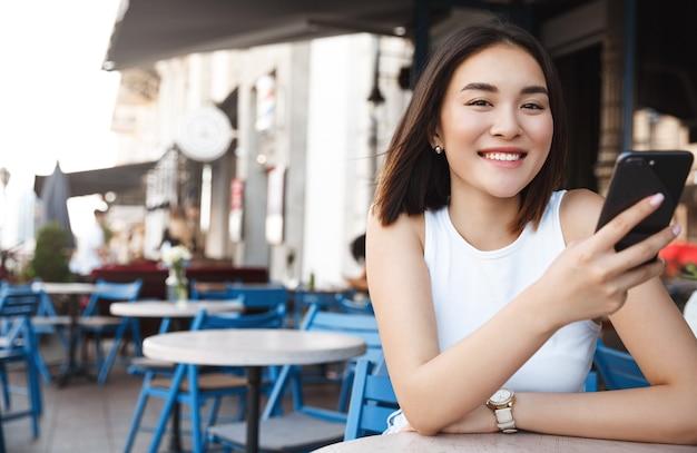 Glimlachende aziatische vrouw die gelukkig kijkt, op terras zit en smartphone gebruikt