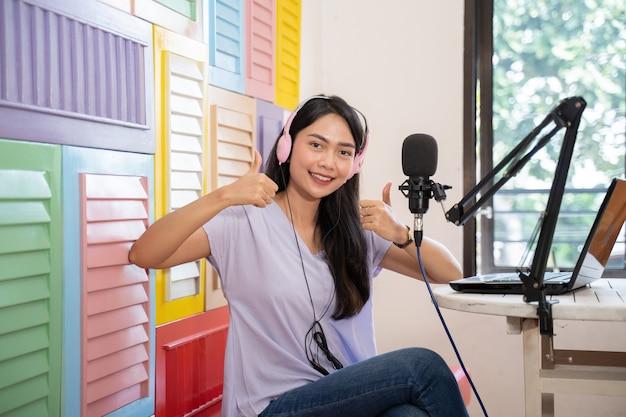 Glimlachende aziatische vrouw die op de bank zit en een koptelefoon draagt die naar de camera kijkt met duimen omhoog
