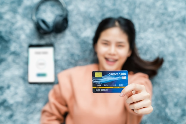 Glimlachende aziatische vrouw die op de vloer ligt en creditcard met mobiele portefeuille-app op digitale tablet houdt.